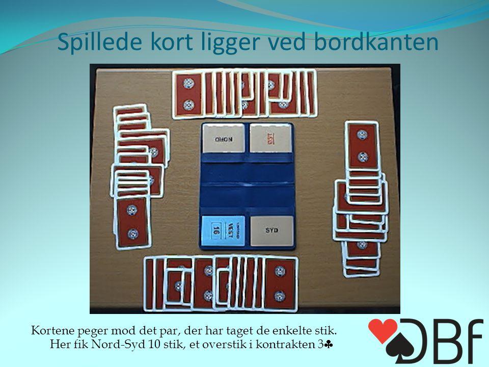 Spillede kort ligger ved bordkanten Kortene peger mod det par, der har taget de enkelte stik.